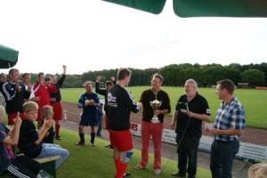 Bürgermeister Ulrich Belde übergibt den Pokal an den TuS Hilter, daneben der 1. Vorsitzende Hans-Hermann Schiebe und Mitorganisator Christian Wöstmann